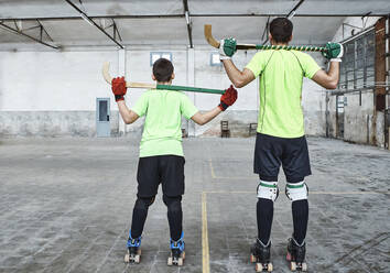 Father and son in sports uniform holding hockey sticks at court - VEGF02831