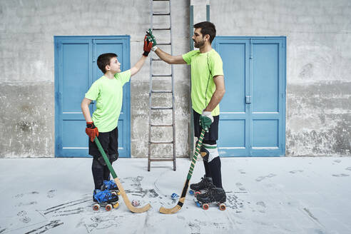Father and son holding hockey sticks while giving high-fives against doors at court - VEGF02837