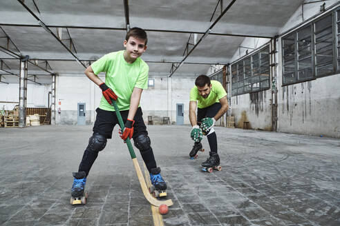 Mature man with son practicing roller hockey on court - VEGF02843