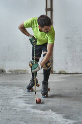 Mature male athlete practicing roller hockey against wall at court - VEGF02846