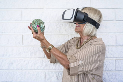Senior woman holding conch, using virtual reality simulator - DLTSF01112