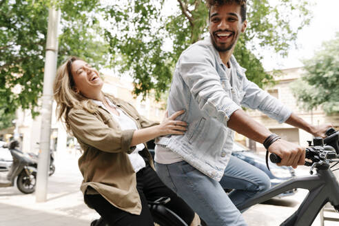 Cheerful young couple enjoying ride on electric bicycle in city - RDGF00128