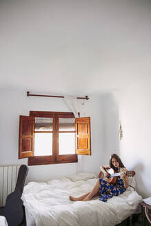 Young woman practicing guitar while sitting on bed at home - LJF01756