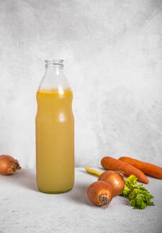 Carrots, onions, celery and bottle of vegetable broth - FLMF00273