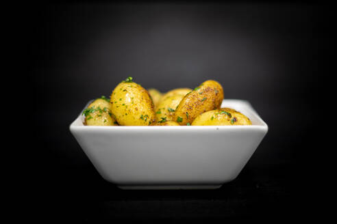 Square bowl of yummy roasted potatoes with herbs placed on black timber table - ADSF12548