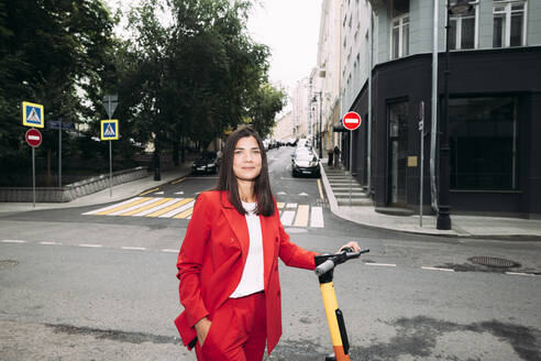 Beautiful businesswoman standing with electric push scooter against street in city - EYAF01305