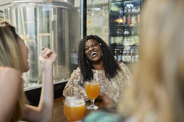 Happy female friends socializing in a pub - ZEDF03638