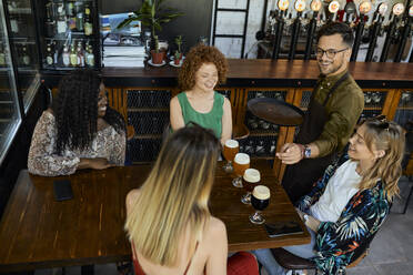 Waiter serving craft beer for female friends in a pub - ZEDF03641