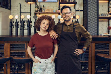 Portrait of confident owner couple at the counter in a pub - ZEDF03686