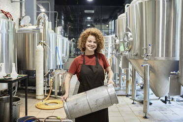 Portrait of smiling woman working in craft brewery - ZEDF03701