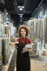 Portrait of confident woman holding clipboard and beer glass in craft brewery - ZEDF03710