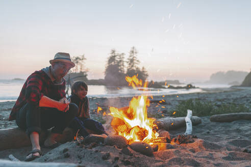 Father and son looking at campfire while sitting on driftwood against sky during sunset - CMSF00131