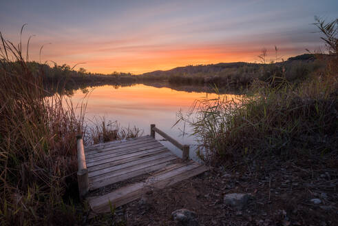 Small wooden pier located on grassy shore of calm pond against cloudy sundown sky in countryside - ADSF12658