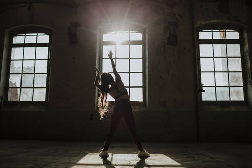 Silhouette of woman exercising while standing at abandoned factory - GMLF00515
