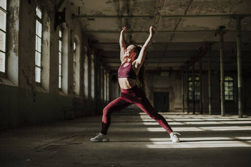 Smiling woman doing crescent lunge exercising at abandoned factory - GMLF00521