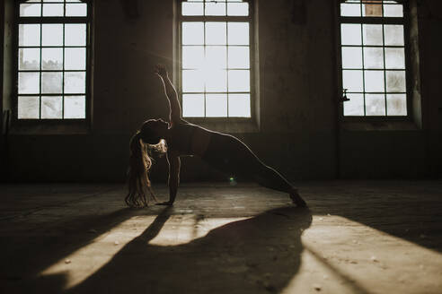Silhouette of woman doing side plank on floor at abandoned factory - GMLF00533
