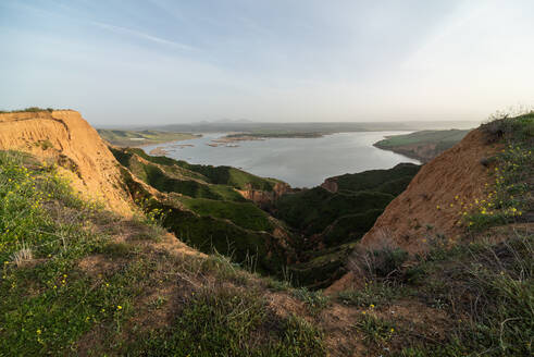 Majestic view of grassy canyon and calm lake located against morning sky in countryside in Barrancas Burujon, Toledo, Spain - ADSF12663