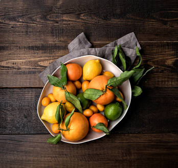 Top view of ripe oranges and mandarins placed in bowl with kumquat and lemon on wooden table with napkin - ADSF12930