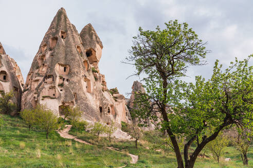 Rock houses of old city located on rough mountain against cloudy sky of Cappadocia, Turkey - ADSF12966