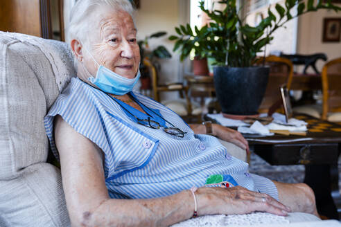 Female senior with protective mask sitting in armchair at home - GEMF04095