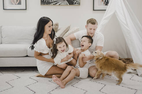 Happy family with dog sitting on floor against sofa at home - SMSF00194