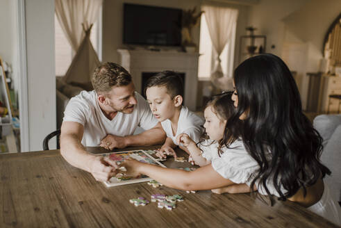 Smiling parents solving jigsaw puzzle with kids over table at home - SMSF00209
