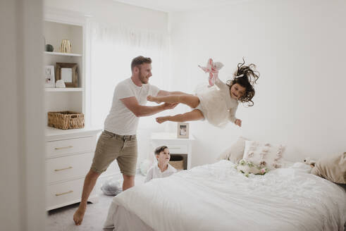 Playful father throwing daughter over bed while son sitting in bedroom - SMSF00218
