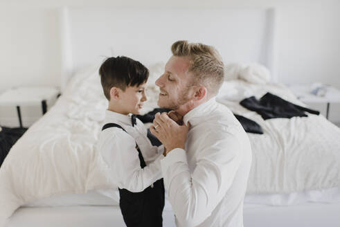 Smiling father and son getting dressed for wedding in bedroom - SMSF00242