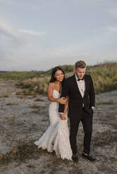 Smiling bridegroom holding hands while walking in field - SMSF00248
