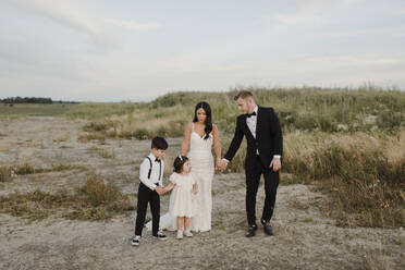 Parents with children wearing wedding dress while standing in field - SMSF00251