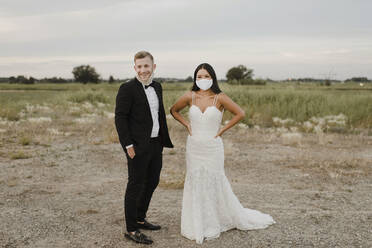 Smiling bride with groom wearing protective face mask while looking away in field during COVID-19 - SMSF00272