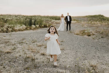 Cute daughter running while parents standing against sky - SMSF00275
