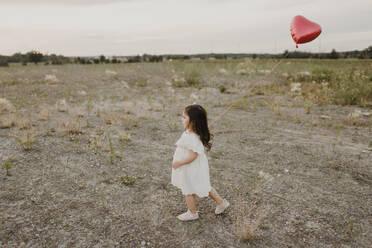 Cute girl with heart shape balloon walking in field - SMSF00278