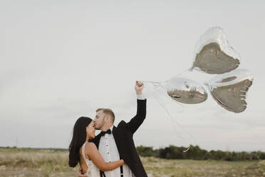 Smiling groom with heart shape balloons kissing bride on forehead against sky - SMSF00281