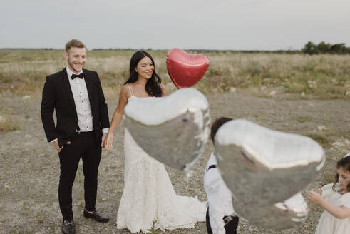 Parents and children wearing wedding dress with heart shape balloons in field against sky - SMSF00287