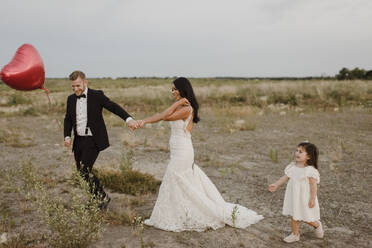 Bride and groom with heart shape balloon holding hands while daughter walking in field - SMSF00290