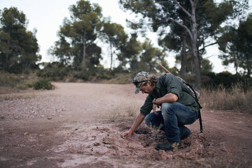 Mature man examining soil in forest - SASF00008