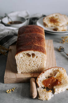 From above piece of tasty Brioche bread on table with loaf on wooden board in kitchen - ADSF13026