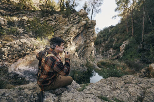 Bushcrafter smoking pipe while sitting on rock formation - SASF00010