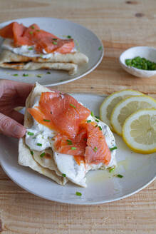 High angle of crop person having lunch and taking flatbread with sour cream and salmon slice garnished with green onion and lemon - ADSF13096