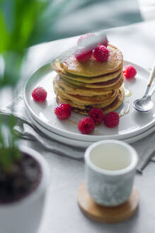 From above plate of delicious pancakes with raspberries placed on napkin near empty cup and potted plant in morning - ADSF13099