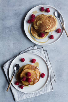 From above top view of tack of tasty pancakes with ripe raspberries placed on plate near spoons on gray background - ADSF13102