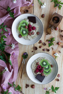 Top view of slices of fresh kiwi and raspberries placed near chocolate and hazelnuts in bowl of healthy porridge on wooden table near lilac cloth - ADSF13114