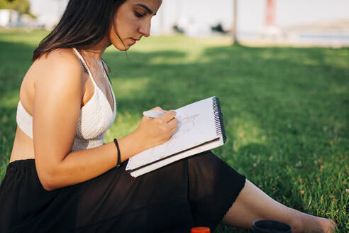 Beautiful woman painting on book while sitting in public park - DCRF00755