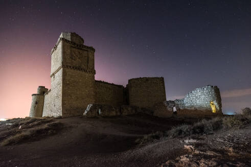 Castle on rough rocky mountain under spectacular scenery with luminous sky stars - ADSF13293