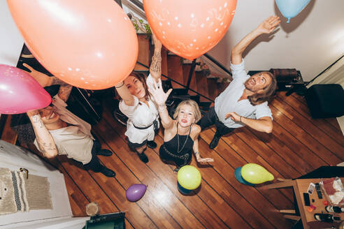 Cheerful friends dancing with colorful balloons during party at home - MEUF02021