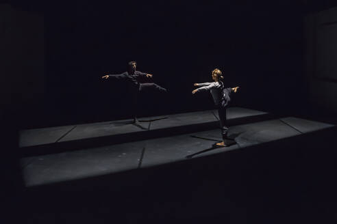 Male and female dancer performing comtemporary ballet on black stage - NGF00606