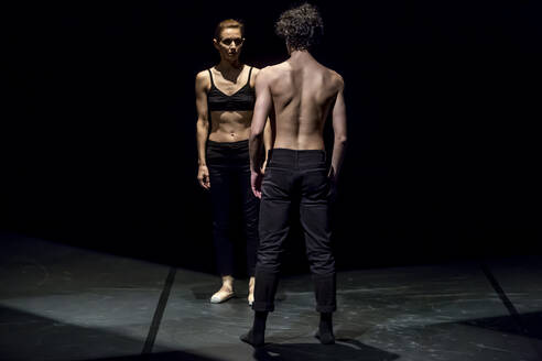 Male and femal dancer performing contemporary ballet on black stage - NGF00618