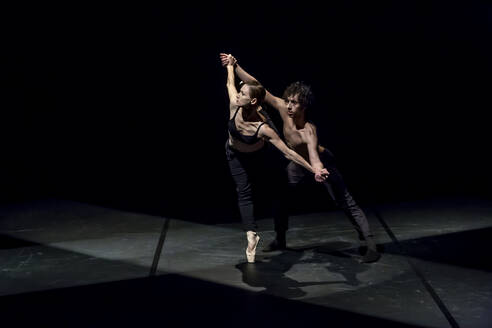 Male and femal dancer performing contemporary ballet on black stage - NGF00621