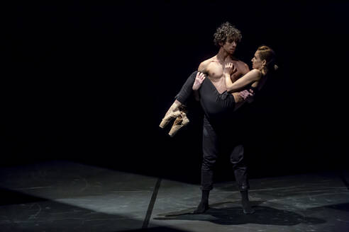 Male and femal dancer performing contemporary ballet on black stage - NGF00624